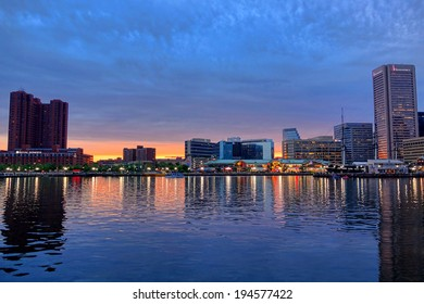 Baltimore, Maryland - Circa 2014: luxury hotels and restaurants with office buildings and shopping mall over waterfront reflections in water on West side of Baltimore Inner Harbor at dusk in Maryland