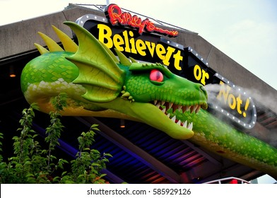 Baltimore, Maryland - July 22, 2013: Smoke blows from the nostrils of a giant green dragon snaked over the entrance to the Ripley's Believe It or Not! Museum at Inner Harbor