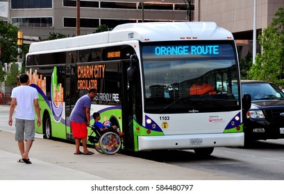 Baltimore, Maryland - July 24, 2013:   Man helps a young boy seated in a wheelchair to board an Orange Route free circulator bus on Pratt Street