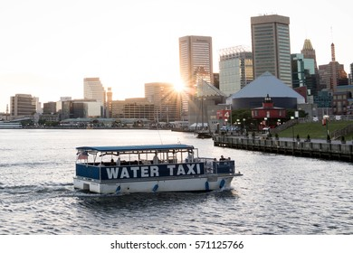 BALTIMORE, MARYLAND - JUNE 12, 2016: Water Taxi in Baltimore Inner Harbor with Skyline in Background at Sunset