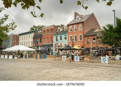 Baltimore, Maryland US - July 31 2020: City urban architecture façade of historic brick buildings along Thames street in downtown Fell's Point neighborhood restaurants and shops for dining and tourist
