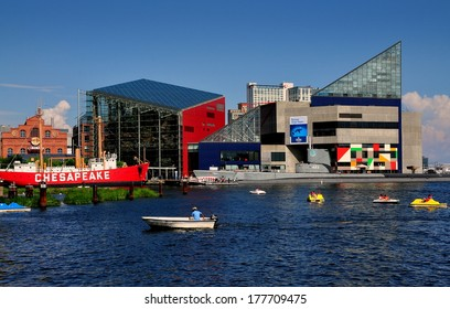 Baltimore, MD - July 22, 2013:  Small boats ply the waters at Inner Harbor in front of the ultra-modern National Aquarium and the Lightship Chesapeake