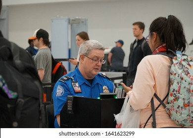 Baltimore, MD, USA - April 8 2019: TSA (Transportation Security Administration) worker checks out passport at the BWI airport.