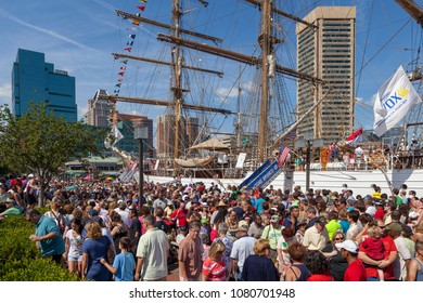 Baltimore, MD, USA - June 16, 2012:  Tourists at a large ship on a summer day in the Inner Harbor of the City of Baltimore, Maryland.