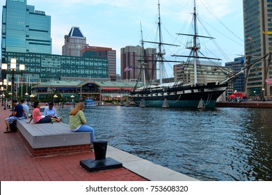 Baltimore, MD, USA June 25, 2014 Folks sit at the waterfront of Inner Harbor in Baltimore, Maryland.  the area, once full of derelict piers is now a shopping and dining destination