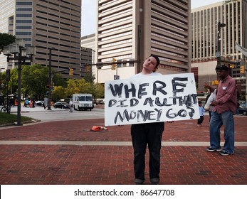 BALTIMORE - OCTOBER 12: An unidentified young man holds a sign with a question at the Occupy Baltimore demonstration in McKeldin Square, at the Inner Harbor on October 12, 2011 in Baltimore, Maryland.