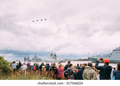 BALTIYSK, RUSSIA - MAY 9, 2015: Celebrating the 70th anniversary of the Victory Day, People on the boardwalk watching the Russian naval fleet