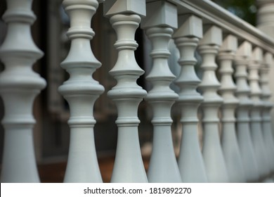 Balusters in the decoration of the veranda railings. An architectural element made of wood. An old manor outside the city. Detail of a building from the last century.