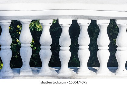 Balustrades. Rows of white stone balusters. Building decoration in classic style. Old weathered architecture details. European garden park landscape design.