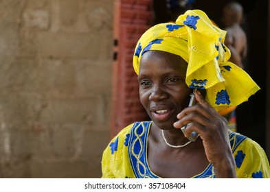 """Bamako - August 12,2013"": Mature black woman speaking with her mobile phone in a rural village near Bamako, Mali"