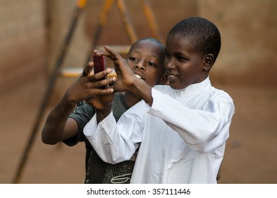 """Bamako - January 5,2014"": Two black boys play with a modern mobile phone in a rural village near Bamako, Mali"