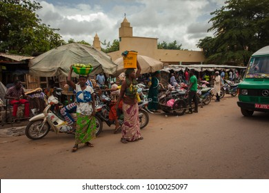 Bamako, Mali - 06 21 2017: Street Scene of Everyday's Life with Women waiting, carrying Goods and a Market in the Background