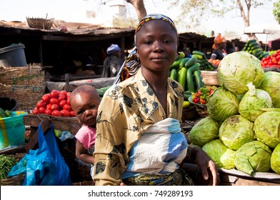 BAMAKO, MALI - CIRCA FEBRUARY 2012: Vegetable seller carrying her daughter on her back in one of Bamako's market.