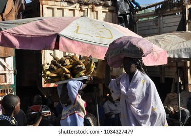 Bamako, Mali - December, 27, 2014: Black african people gathering and preparing object for selling at the market morning opening.
