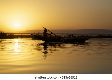 BAMAKO, MALI, JANUARY 5: Silhouette of young african man traveling on his small wooden boat on the River The Niger in Bamako during a beautiful sunset. Mali 2011