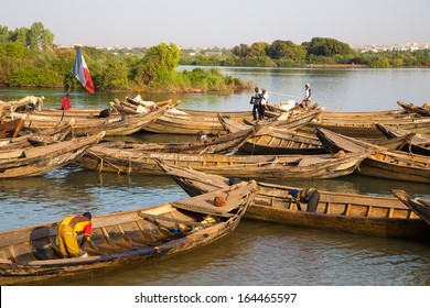 BAMAKO, MALI, JANUARY 7: Unidentified fisher men working in their boat on the Niger River in Bamako with the countryside in the background. Mali 2011