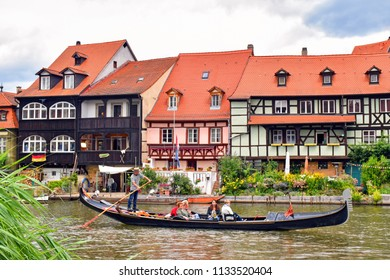 Bamberg, Germany - July 12, 2018: A gondolier with a Venetian gondola moves passengers on the river Regnitz along historic half-timbered houses in the old town of Bamberg (Germany).