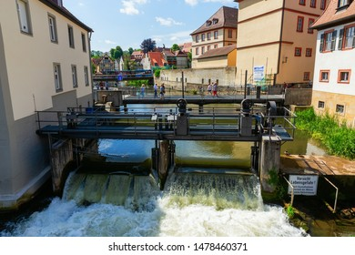 Bamberg, Germany - June 14, 2019: weir on the river Regnitz in Bamberg, Bavaria, with unidentified people. Bamberg is a city in Bavaria and well known for its medieval old town