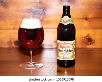Bamberg, Germany - March 1 2019: Dark Bamberg Smoked Beer from the famous Spezial Brewery in Bamberg, Bavaria, Germany in the Glass with its Bottle on a wood table.