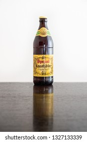 Bamberg, Germany - March 1 2019: A bottle of Bamberg Smoked Beer from the famous Spezial Brewery in Bamberg, Bavaria, Germany on a dark wooden table against a white background.