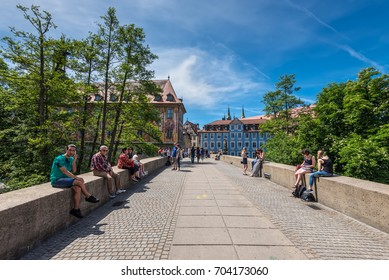 Bamberg, Germany - May 22, 2016: People seating and passing by bridge in downtown of Bamberg, Upper Franconia, Bavaria, Germany. Bamberg is under UNESCO protection.