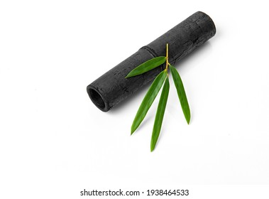 Bamboo activated charcoal sticks and green leaf isolated on white background