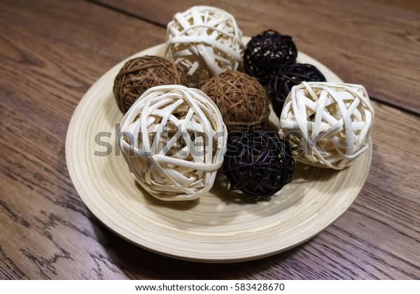 Bamboo ball are 3 color (white, black and brown)  on laminate dish wood with brown wood table in background. Kitchen and copy space in photo.