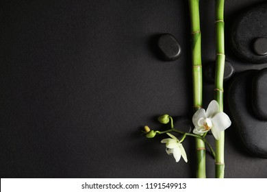 Bamboo branches with flowers and spa stones on black background, top view. Space for text