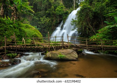 Bamboo bridge across river over the beautiful waterfall in deep forest, Chaing Mai, Thailand