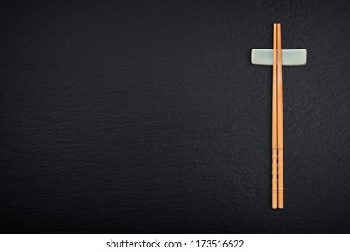 Bamboo chopsticks with copy space on black slate background, top view