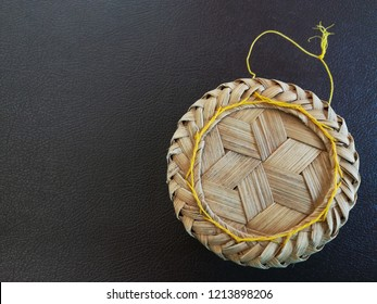 Bamboo container for streamed sticky rice on brown table. Handicraft with wood stripes produce housewares.