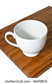 Bamboo cutting board with tea cup isolated on white.