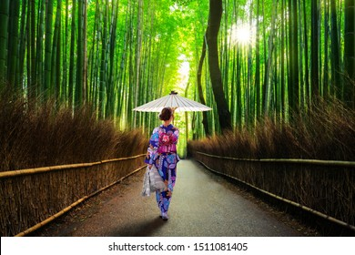 Bamboo forest at Arashiyama with woman in traditional kinono and umbrella. Japan