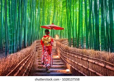 Bosque de Bambú. Mujer asiática usando kimono tradicional japonés en el bosque de Bambú en Kioto, Japón.