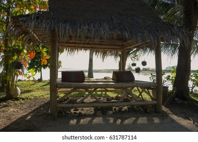 Bamboo gazebo for relaxing atmosphere near the sea. Couch trestle-bed during sunset