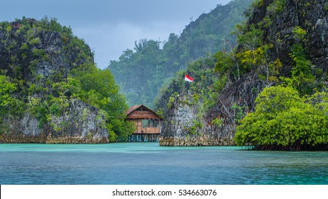 Bamboo Hut between some Rocks under Rain in Bay, Painemo Islands, Raja Ampat, West Papua, Indonesia