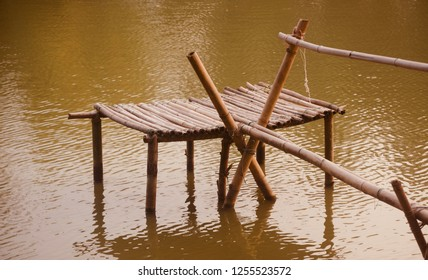 A bamboo made sitting place on top of a lake unique photo