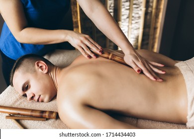 Bamboo massage. The massaeur doing massage of male client using hollow bamboo cane rolling on back oily hands close-up. Body care, skin care, wellness, wellbeing, beauty treatment concept.