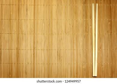 Bamboo mat and chopsticks food background