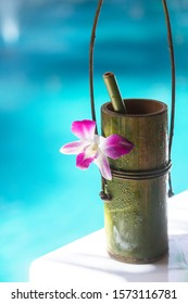 Bamboo natural cup with small bamboo tube, docorate with purple flower, tie together with vine. Blue pool on background - vertical