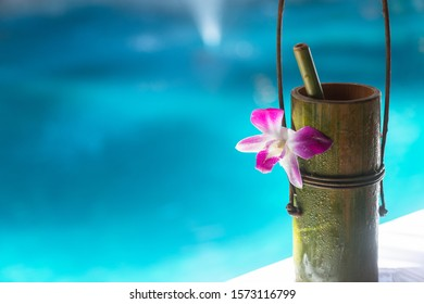 Bamboo natural cup with small bamboo tube, docorate with purple flower, tie together with vine. Blue pool on background