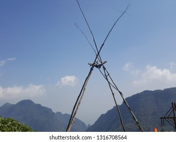 Bamboo pillars for tribal swings, mountain and sky backdrop