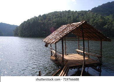 A bamboo raft set in a lake surrounded by mountains and trees. It is a quiet and relaxing place.