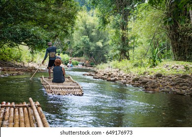 Bamboo rafting in green tropical scenery as a tour for tourist in Thailand