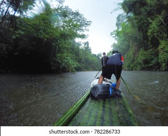 Bamboo rafting in river while raining, adventure rafting, in jungle of Thailand.