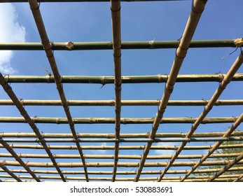 Bamboo roof construction with blue sky.