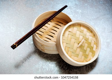 Bamboo steamer and chopsticks on a stone beige background
