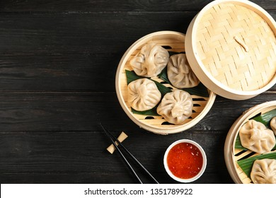 Bamboo steamers with tasty baozi dumplings, chopsticks and bowl of sauce on wooden background, top view. Space for text