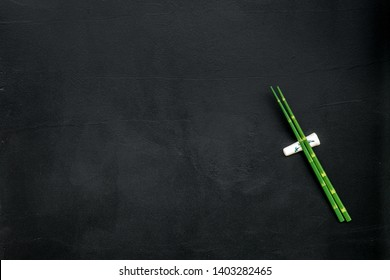 bamboo sticks for sushi and maki on black background top view mockup