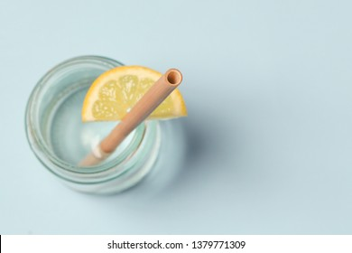 Bamboo straw in a glass of lemon water on the blue background, Reusable bamboo straws as an alternative for single-use plastic straws, healthy and sustainable lifestyle concept